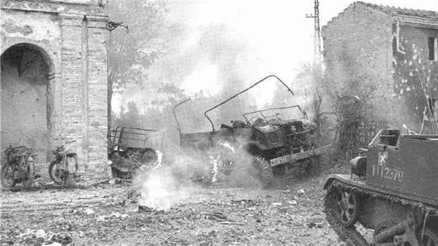 A Canadian 15cwt CMP truck and a jeep burn after a hit by a German mortar. The Germans had carefully established firing lines making the battle extremely fierce and deadly. Another Canadian designed vehicle- Universal carrier (aka bren carrier) is in the foreground