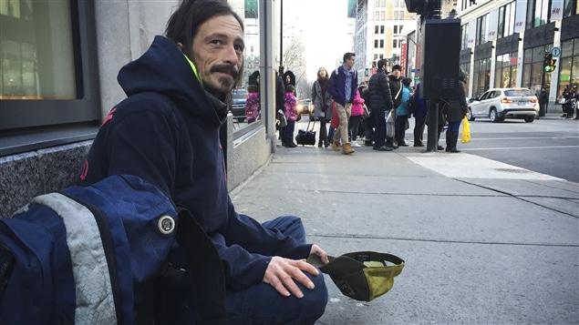 Stephan quête sur la rue Peel, dans le centre-ville.