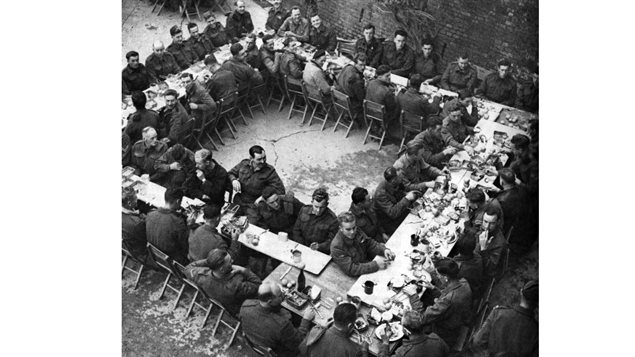 The Seaforth Highlanders enjoy their Christmas dinner, in the bombed-out church at Santa Maria di Constantinopoli, Ortona, Italy, 25 December 1943.
