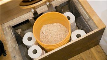 Un système de toilette compostable qui utilise des sciures de bois.