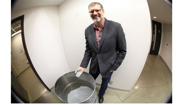 Professor Jeffrey Bergthorson with his hand covered after dipping it in the barrel filled with finely ground aluminium powder fuel.
