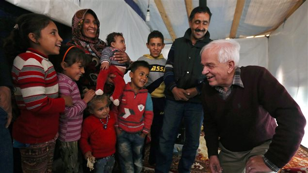 Canadian Minister of Immigration John McCallum, right, speaks with a Syrian family inside their tent, during his visit to a refugee camp in the southern town of Ghaziyeh, near the port city of Sidon, Lebanon, Friday, Dec. 18, 2015.