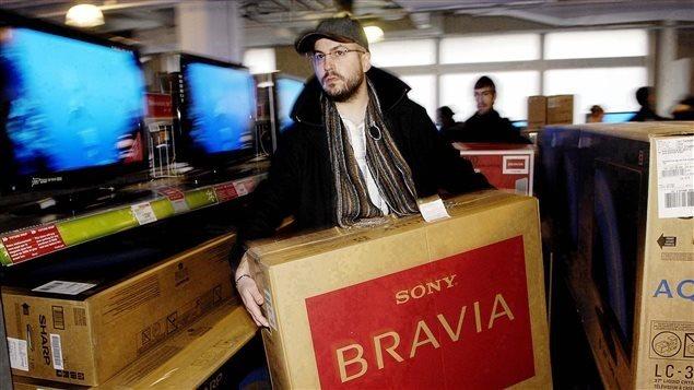 Un homme s'achète un téléviseur pendant les soldes d'après Noël.