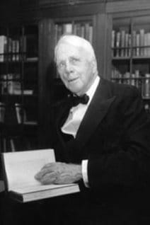 Robert Frost, a elderly, handsome man with milk-white hair, sits in his library in a dark suit and bow tie. His left hand is placed on a book that is partially open.