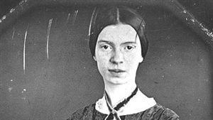 Emily Dickinson sits facing a camera being photographed in black and white. Her dark hair is parted in the middle and is swept back in a tight bun. She has pale skin and kind, dark eyes.