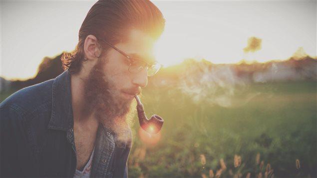 Hipster qui fume sa pipe.
