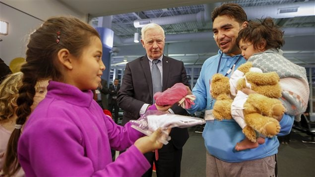 The Governor General of Canada David Johnston greets Syrian refugees as his granddaughter Tea gives a man and his daughter a toque at the Pearson Toronto International Airport in Mississauga, Ontario, December 18, 2015.