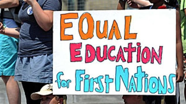 "Aboriginal students in ten B.C. provincial districts are graduating less than 50 percent of the time, even though the provincial goal has set a graduation goal of 85 per cent. We see students holding a sign that says ""Equal Education for First Nations."" The lettering is orange red and light blue."