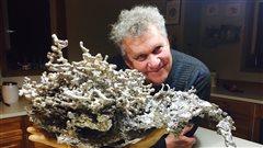 Pierre Bolduc pose avec sa sculpture reproduisant un nid de fourmis.