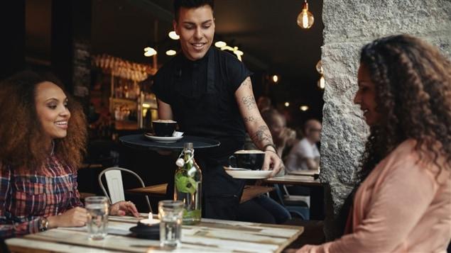 Un serveur sert deux clientes dans un restaurant.