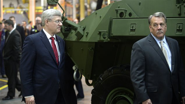 Former Prime Minister Stephen Harper walks past a Light Armoured Vehicle 6.0 during a photo opportunity at General Dynamics Land Systems in London, May 2, 2014.