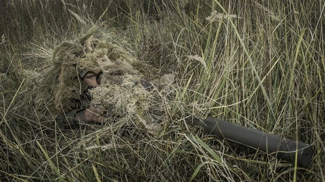 A sniper from Joint Task Force Ukraine takes a concealed position prior to shooting on a range with a C14 Timberwolf rifle at the International Peacekeeping and Security Centre (IPSC) in Starychi, Ukraine on November 2, 2015 during during Operation UNIFIER.