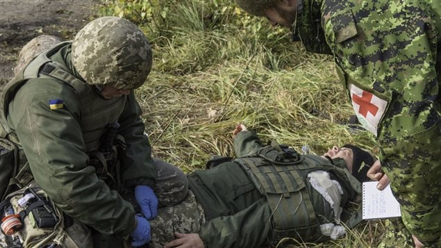 A medical member of 2 Field Ambulance supervises the Combat First Aid applied by Ukrainian soldiers in training during Operation UNIFIER at the International Peacekeeping and Security Centre (IPSC) in Starychi, Ukraine on October 30, 2015.
