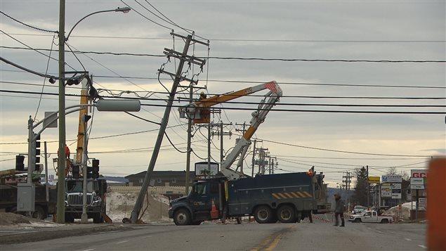 Une équipe d'Hydro-Québec tente de redresser un poteau.