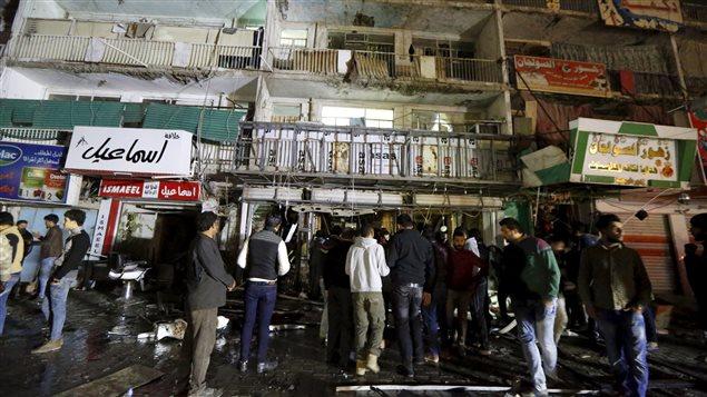 Des Irakiens rassemblés sur le site du centre commercial de Bagdad dont l'attaque a été revendiquée lundi par l'État islamique.