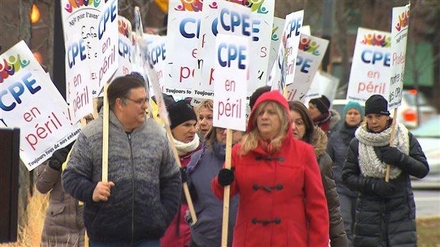 Des éducateurs et éducatrices en CPE manifestent aux abords du pont Jacques-Cartier.