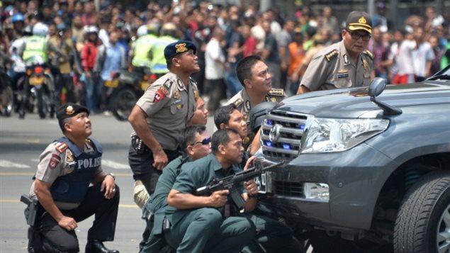 Des policiers indonésiens prennent position derrière un véhicule alors qu'ils poursuivent des suspects après une série d'attentats à Jakarta.. (AFP / Getty Images)