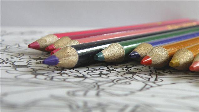 Des crayons de couleurs et un dessin à colorier