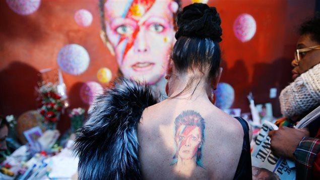 À Londres, une femme arbore un tatouage de Ziggy Stardust devant une murale représentant le personnage qu'incarnait David Bowie, où a grandi la légende du rock.