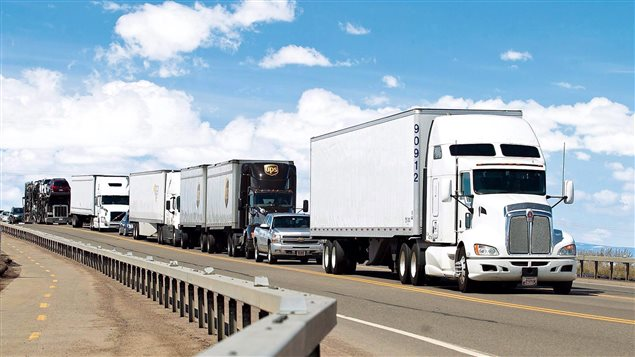 Trucks hauling cargo from Canada through the United States to Mexico make their way to Wyoming Highway 30 on Tuesday, April 21, 2015, in Laramie, Wyo.