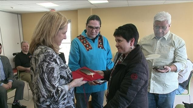 Aboriginal elder Claudette Commanda presents an eagle feather to Jan Crozier, supervisor of operations at the courthouse in the nation's capital, Ottawa.