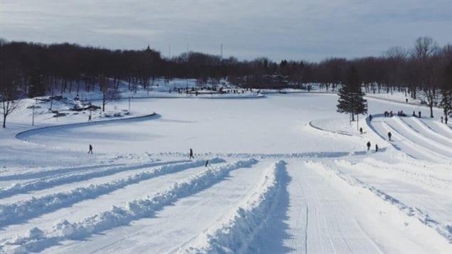 La patinoire naturelle du Lac aux Castors est déserte, de même que la majorité des glissades, interdites. En arrière-plan, les patineurs se massent sur la patinoire artificielle.