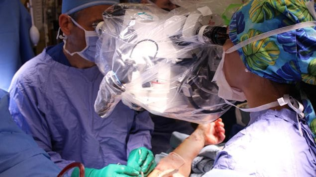 With arteries attached, Dr. Stefan Hofer (L) and Dr. Toni Zhong (R), both plastic surgeons, move on to attach the blood vessels