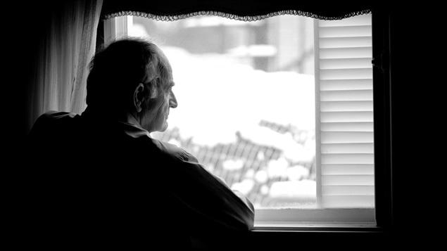 Un homme regarde par la fen�tre.