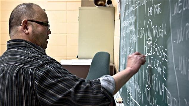 Un professeur donne un cours de francisation à de nouveaux arrivants.