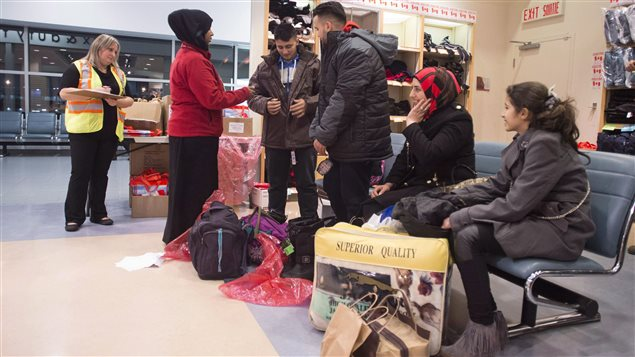 Members of a Syrian family are given new winter coats as they arrive at the Welcome Centre at Toronto's Pearson Airport on Friday December 18, 2015.