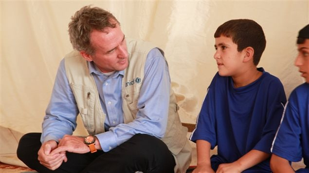 UNICEF Representative Robert Jenkins chats with children participating in psychosocial sports programmes at a UNICEF supported child centre in Za'atari camp – 2014. Photo: UNICEF Jordan/miraj