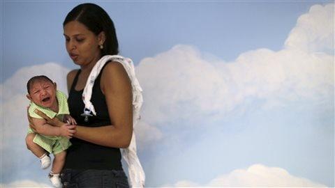 Une Brésilienne tient son bébé, qui souffre de microcéphalie, lors d'un exercice visant à assurer le développement correct de sa vision.
