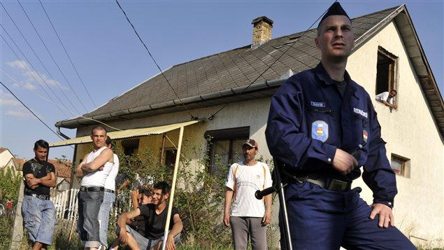 In April 2011, a Hungarian police officer guarded a Roma neighbourhood close to a site where vigilante groups set up a training camp. Threats from vigilantes and discrimination prompted some Roma to flee Hungary.