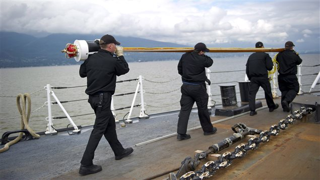 Crew prepare to raise a flag pole during a tour given by the Canadian Navy of HMCS Winnipeg in Vancouver, B.C., on Tuesday, June 10, 2014.