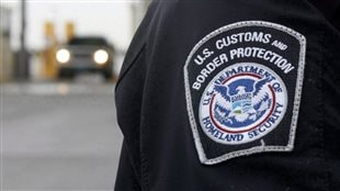 A U.S. Customs and Border Protection (CMP) officer stands near a security booth as vehicles approach in Detroit, Michigan, on June 1, 2009.