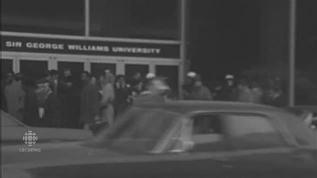 Police in white helmets and crowds milling around the occupied Sir George Williams University in 1969. in downtown Montreal.