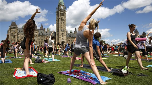 People practice yoga on the west lawn of Parliament Hill in Ottawa July 16, 2014.