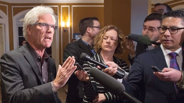 Natural Resources Minister Jim Carr is vowing to work closely with First Nations on low carbon energy projects. We see a grey-haired man with snow-white hair dressed in a sports jacket and open shirt speaking a media scrum. Wearing rimless glasses, he looks professorial. He gestures with his right hand to a see of microphones surrounding him.
