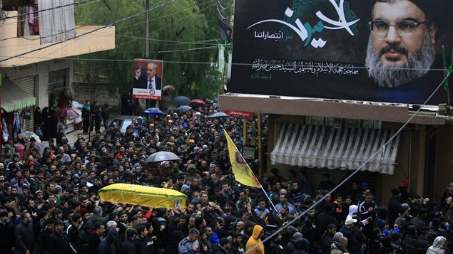 Relatives and comrades carry the coffin of Hezbollah member Ali Ahmad Sabra, who was killed on Friday during an offensive by Syrian troops and Hezbollah fighters in Syria, during his funeral procession in Jibchit, southern Lebanon, Saturday, Feb. 6, 2016. A billboard shows Hezbollah leader Sheik Hassan Nasrallah with Arabic that reads, *Al Hussein the secret of our victories.*