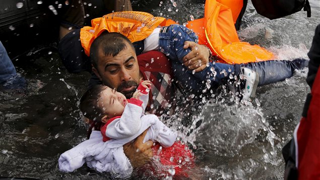 A Syrian refugee holds onto his children as he struggles to walk off a dinghy on the Greek island of Lesbos, after crossing a part of the Aegean Sea from Turkey to Lesbos, September 24, 2015.