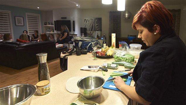 Carolane Lauzière s'affaire à préparer une repas à domicile tandis que les convives discutent au salon.