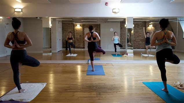 Rachael Allen, centre, an instructor at Iam Yoga, teaches a class of hot yoga in Toronto on Wednesday, December 17, 2014.