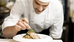 Un jeune chef dresse une assiette.