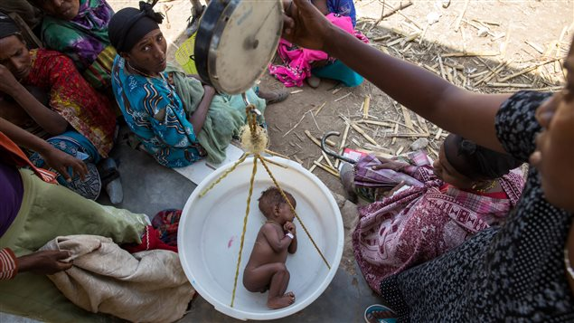 A baby is weighed on a scale in Ethiopia. Two seasons of failed rains mean that nearly six million children across Ethiopia currently require food assistance.