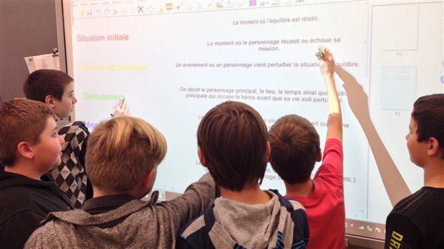 Des élèves de sixième année de l'école Douville à Saint-Hyacinthe utilisent le tableau interactif installé dans leur classe.