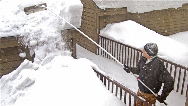 Un homme en train d'utiliser une pelle à toiture avec un manche télescopique.