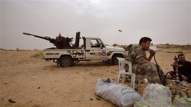 In this Saturday, Feb. 21, 2015 photo, Libyan soldiers take a break from fighting with militants on the frontline in Al Ajaylat, 120 kilometers west of Tripoli, Libya.