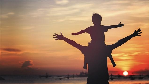 Un père transporte son enfant sur ses épaules.