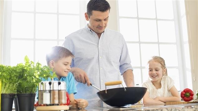 Un p�re cuisine avec ses enfants.