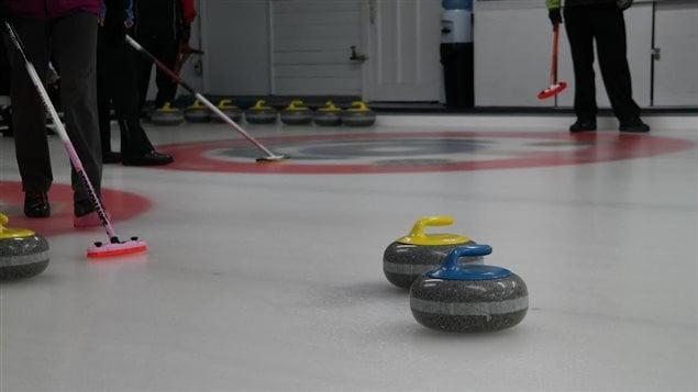 Des joueurs de curling et leurs pierres